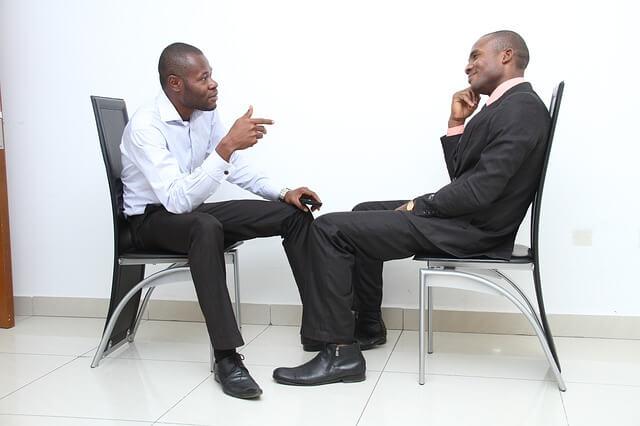 Mężczyźni siedzą przy stole i debatują