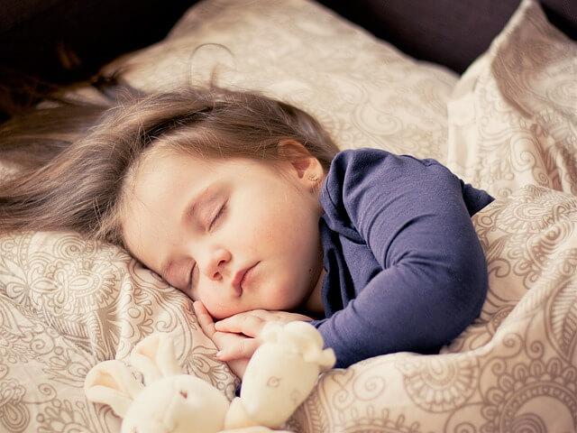Dziecko śpi w beżowo-złotej pościeli