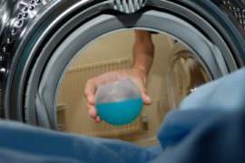 Kobieta wsypuje proszek do bębna pralki