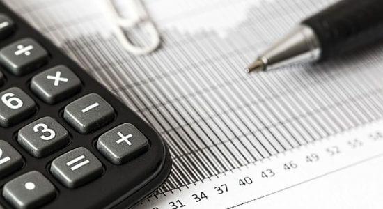 Kartka papieru z kalkulatorem i długopisem