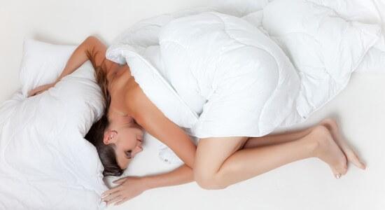 Kobieta śpi w białej pościeli