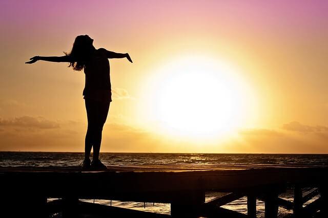Kobieta stoi na molo i wystawia sylwetkę do słońca