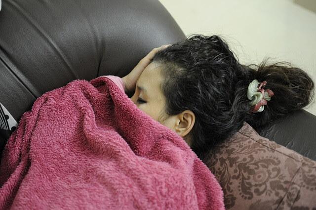 Kobieta śpi przykryta różowym kocem