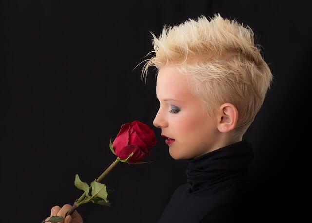 Blondwłosa kobieta wącha czerwoną różę