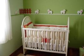 Białe łóżeczko dla dziecka w zielonym pokoju