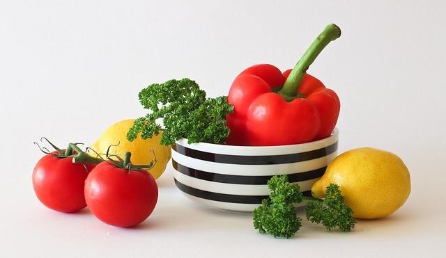 Papryka i brokuły na misce, obok pomidor i cytryna