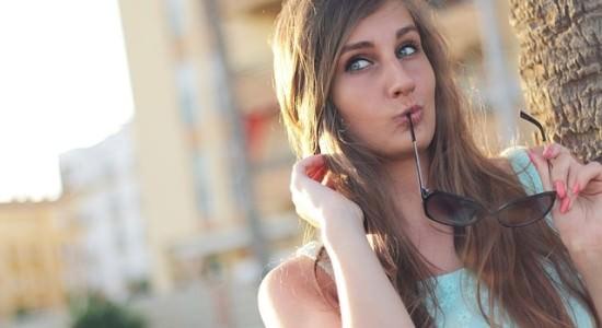 Kobieta trzymająca w ustach okulary przeciwsłoneczne