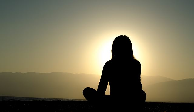 Siedząca na ziemi kobieta patrząca w stronę słońca