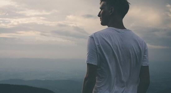 Stojący na szczycie mężczyzna spoglądający w dal