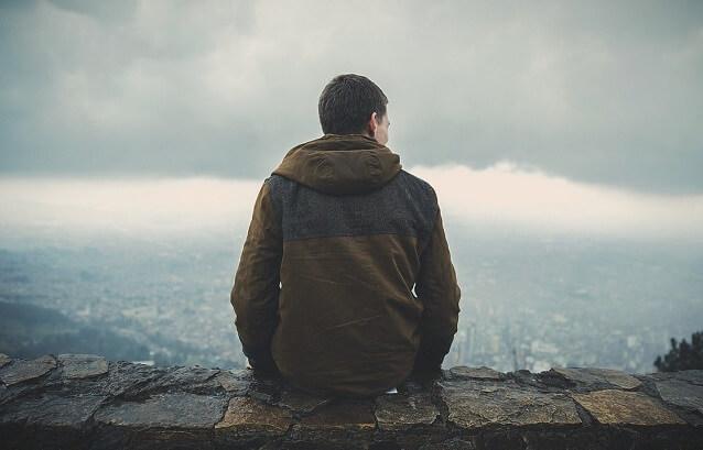 Mężczyzna siedzący na murze
