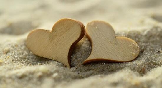 Dwa drewniane serca leżące na plaży