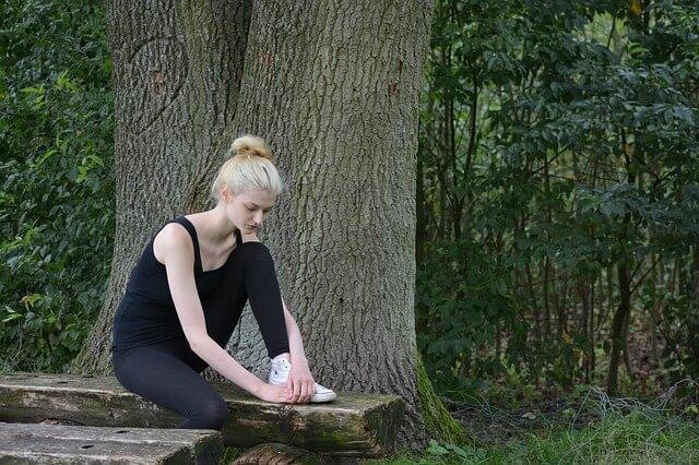 Blondwłosa dziewczyna na ławce w lesie