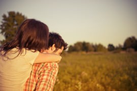 Dziewczyna obejmuje chłopaka za szyje na tle popołudniowego słońca