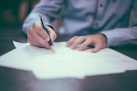 Ręka wypełniająca dokumenty do becikowego