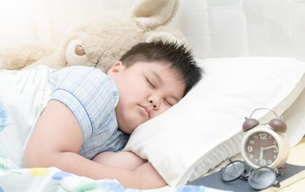 Chłopiec śpi w łóżku