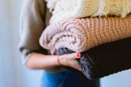 Kobieta trzymająca swetry
