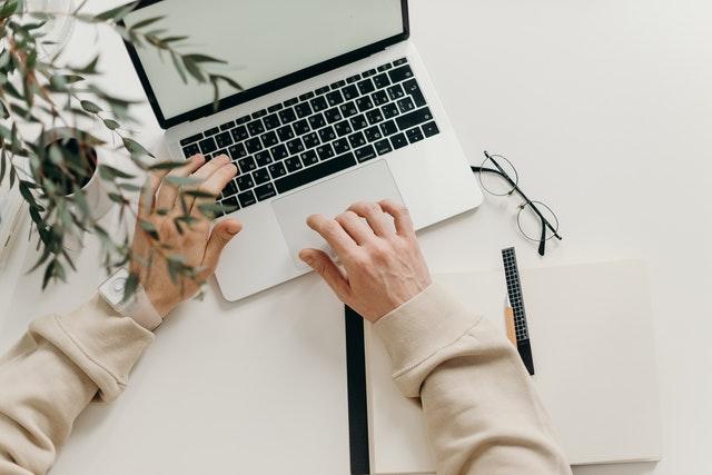 mężczyzna piszacy na laptopie